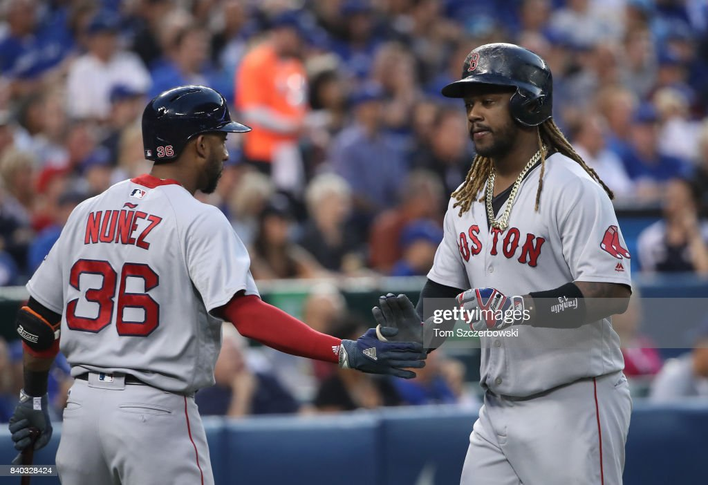 Hanley Ramirez #13 of the Boston Red Sox is congratulated by Eduardo Nunez #36 after scoring a run on a throwing error in the second inning during MLB game action against the Toronto Blue Jays at Rogers Centre on August 28, 2017 in Toronto, Canada.