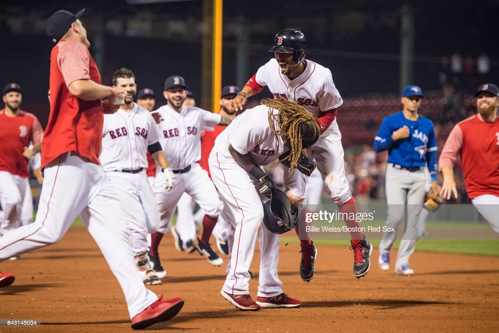 Hanley Ramirez #13 of the Boston Red Sox is mobbed by Mookie Betts #50 and teammates during the nineteenth inning of a game against the Toronto Blue Jays on September 5, 2017 at Fenway Park in Boston, Massachusetts.
