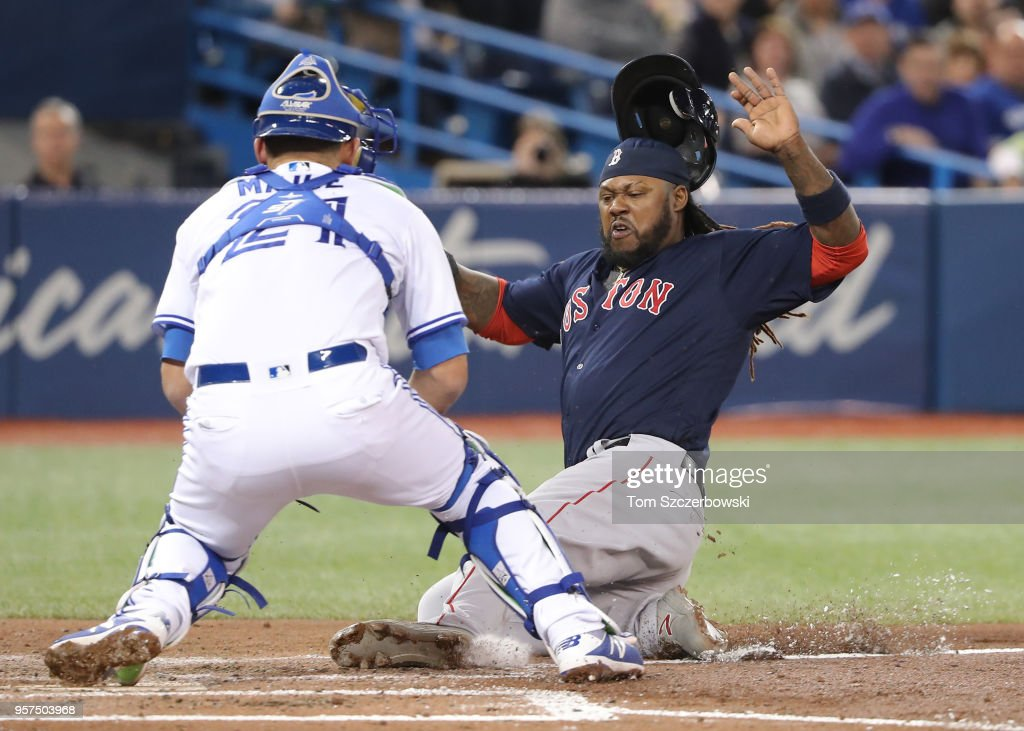 Hanley Ramirez #13 of the Boston Red Sox is thrown out at home plate in the third inning during MLB game action as Luke Maile #21 of the Toronto Blue Jays prepares to tag him out at Rogers Centre on May 11, 2018 in Toronto, Canada.