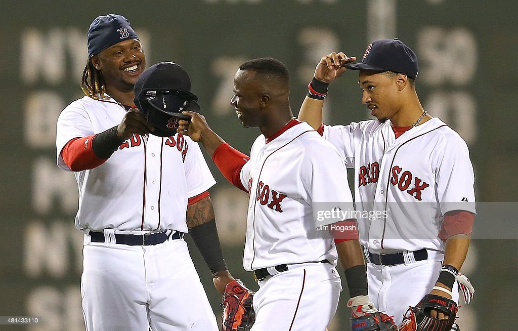 Hanley Ramirez #13 of the Boston Red Sox, Mookie Betts #50, Rusney Castillo #38 celebrate a 9-1 win over the Cleveland Indians at Fenway Park on August 18, 2015 in Boston, Massachusetts.