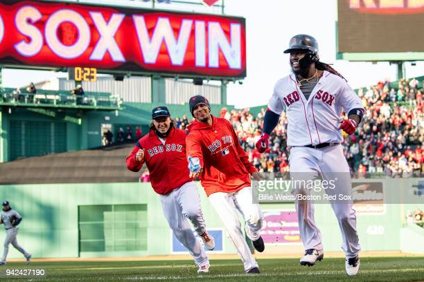 Hanley Ramirez of the Boston Red Sox reacts with Brock Holt and Marco Hernandez after hitting a game winning walkoff single during the twelfth inning...