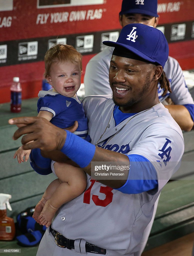 Hanley Ramirez #13 of the Los Angeles Dodgers holds a baby in the dugout before the MLB game against the Arizona Diamondbacks at Chase Field on August 27, 2014 in Phoenix, Arizona.
