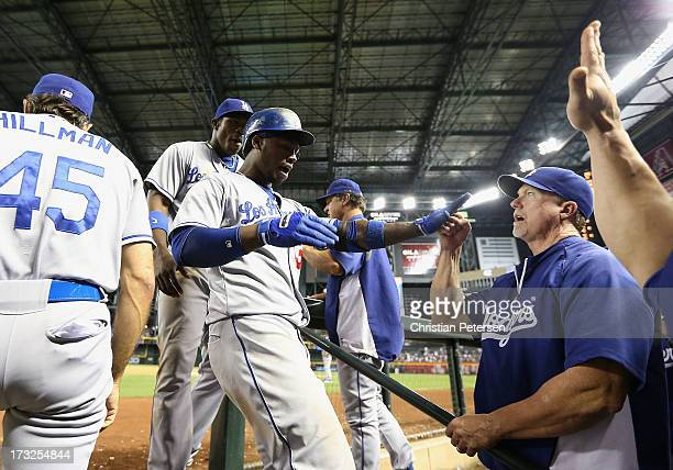 Hanley Ramirez of the Los Angeles Dodgers is congratulated by batting coach Mark McGwire and teammates in the dugout after hitting a solo home run...