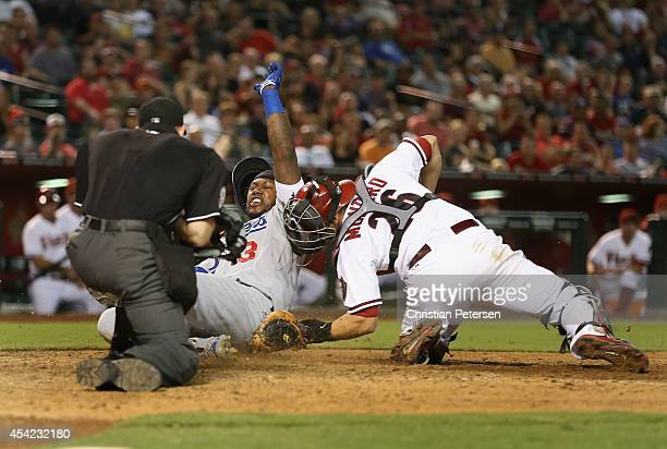 Hanley Ramirez of the Los Angeles Dodgers safely slides in to score a run past catcher Miguel Montero of the Arizona Diamondbacks during the seventh...