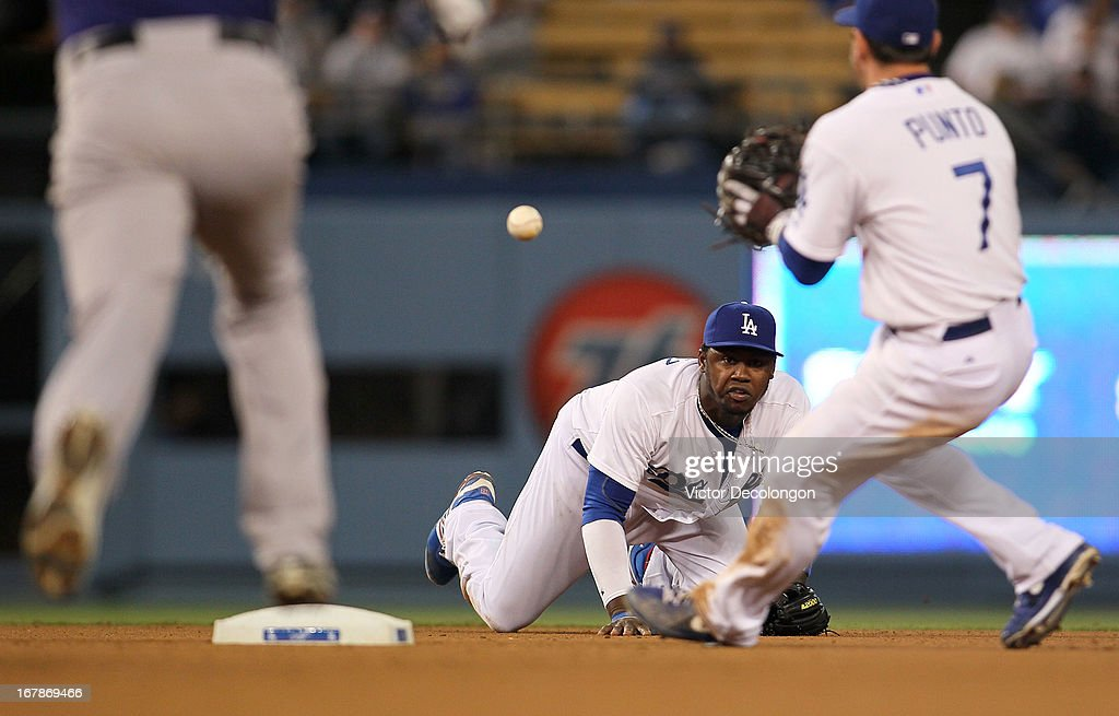 Hanley Ramirez #13 of the Los Angeles Dodgers tosses the ball to teammate Nick Punto #7 to start the double play in the eighth inning during the MLB game against the Colorado Rockies at Dodger Stadium on April 30, 2013 in Los Angeles, California. Punto got Josh Rutledge #14 of the Colorado Rockies on the force out at second and threw out Carlos Gonzalez #5 of the Colorado Rockies at first base to complete the double play. The Dodgers defeated the Rockies 6-2.