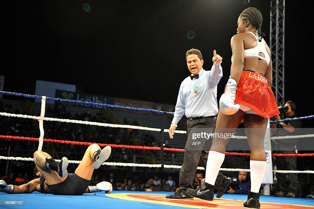 Hanna Gabriel (L) of Costa Rica lies on the ring floor after being knocked down by Oxandia Castillo of the Dominican Republic during their World Boxing Organization super welterweight bout in San Jose on February 28, 2013. Oxandia won after round two by tecnical knockout. AFP PHOTO / Ezequiel BECERRA