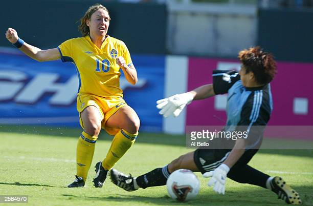 Hanna Ljungberg of Sweden kicks for a goal over the defense of goalkeeper Silke Rottenberg of Germany during the FIFA Women''s World Cup Final on...