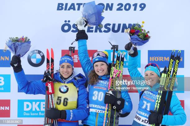 Hanna Oeberg of Sweden celebrates winning the gold medal ahead of Laura Vittozzi of Italy and Justine Braisaz of France during the flower ceremony...