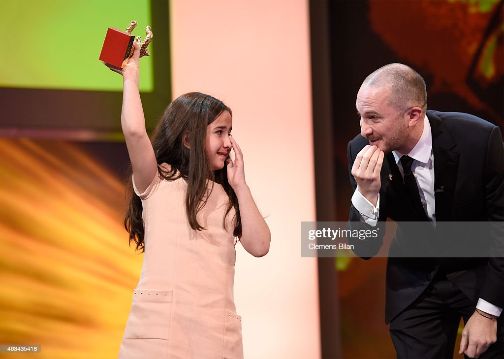 Hanna Saedi accepts the golden bear for 'Taxi' on behalf of her uncle Jafar Panahi with Jury president Darren Aronofsky during the Closing Ceremony of the 65th Berlinale International Film Festival at Berlinale Palace on February 14, 2015 in Berlin, Germany.
