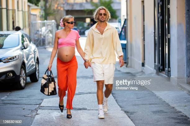 Hanna Stefansson wearing pink cropped top, orange trousers and Frederik Darre wearing white shorts, yellow shirt are seen outside Samsøe & Samsøe...