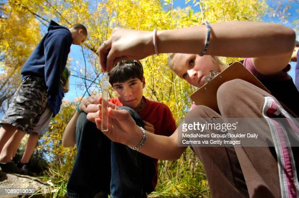 Hanna Thompson right, puts a capsule into a vial of creek water to test the pH level under the watchful eye of Ryan McClure as other students from...