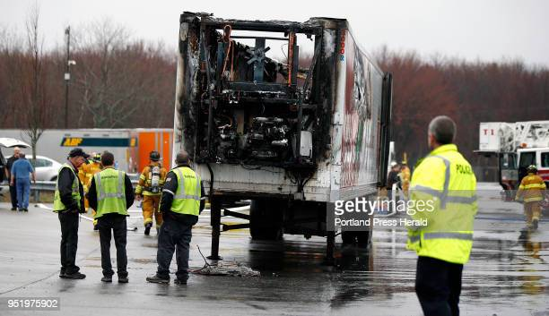 Hannafords employees and emergency responders surround a refrigerated truck trailer that caught fire Thursday at Hannaford Distribution Center...