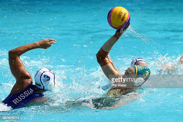 Hannah Buckling of Australia passes over Ekaterina Prokofyeva of Russia during the Preliminary Round Group A Womens Waterpolo match between Russia...