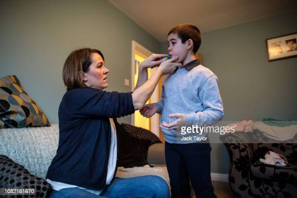 Hannah Deacon helps her son Alfie to brush his teeth at their home on January 13 2019 in Kenilworth England Alfie Dingley aged seven suffers from...