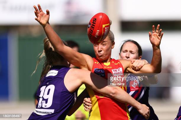 Hannah Dunn of the Suns contests for the ball against Hayley Miller and Kara Antonio of the Dockers during the round four AFLW match between the...
