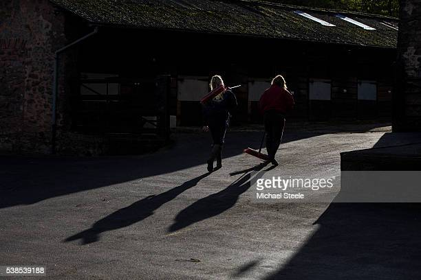 Hannah Halstead and Beth Childs on sweeping up duty at Sandhill Racing Stables on November 23 2015 in Minehead England Sandhill Racing Stables set in...