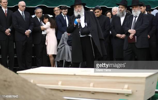 Hannah Kaye daughter of shooting victim Lori Gilbert Kaye is held by her father Howard Kaye as wounded Rabbi Yisroel Goldstein speaks above the...