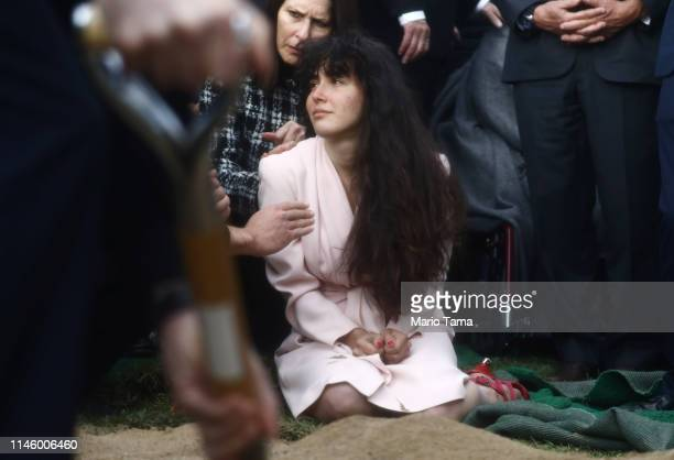 Hannah Kaye daughter of shooting victim Lori Gilbert Kaye mourns at her mother's grave during a graveside service on April 29 2019 in San Diego...
