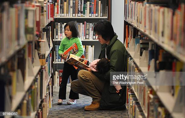 GERMANTOWN MD Hannah Lee grabs a book as her dad Samson Lee holding her sleeping sister 1yearold Jenna at the Germantown Library in Maryland on...