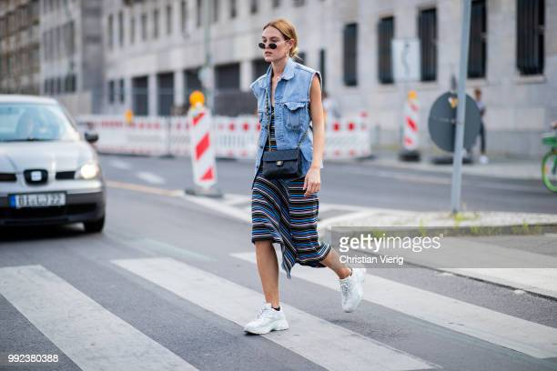 Hannah Pot d'Or wearing sleeveless denim vest striped dress seen outside Lana Mueller during the Berlin Fashion Week July 2018 on July 5 2018 in...
