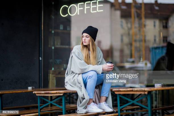 Hannah Pot d'Or with a coffee to go in her hands wearing white Reebok sneakers Levis denim jeans Urban Outfitters sweater vintage coat black wool hat...