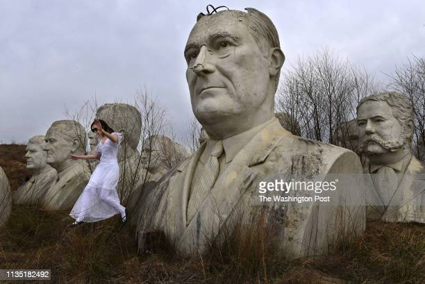 Hannah Rice jumps from a stump after posing for a photograph next to a statue of President Franklin Delano Roosevelt as she and others take part in a...