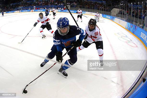 HannaRiika Valila of Finland skates with the puck against Phoebe Stanz of Switzerland during the Women's Ice Hockey Preliminary Round Group A game on...