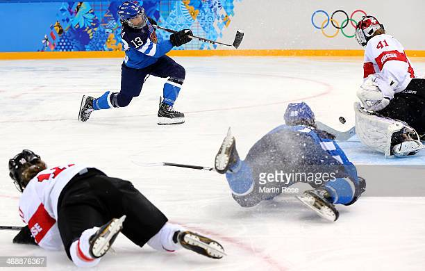 Hanna-Riika Valila of Finland takes a shot on goal against Florence Schelling of Switzerland in the first period during the Women's Ice Hockey...