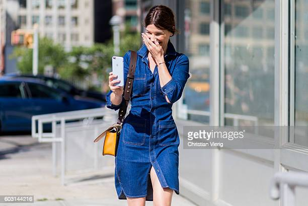 Hanneli Mustaparta laughing while taking photos with her phone wearing denim dress and Prada bag outside J Crew on September 11 2016 in New York City