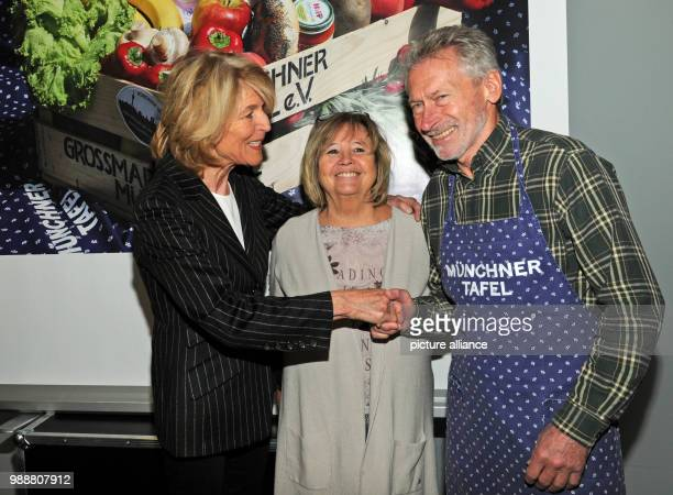 Hannelore Kiethe president and founder of Munchner Tafel eV greeting former national soccer player Paul Breitner and his wife Hildegard ahead of the...