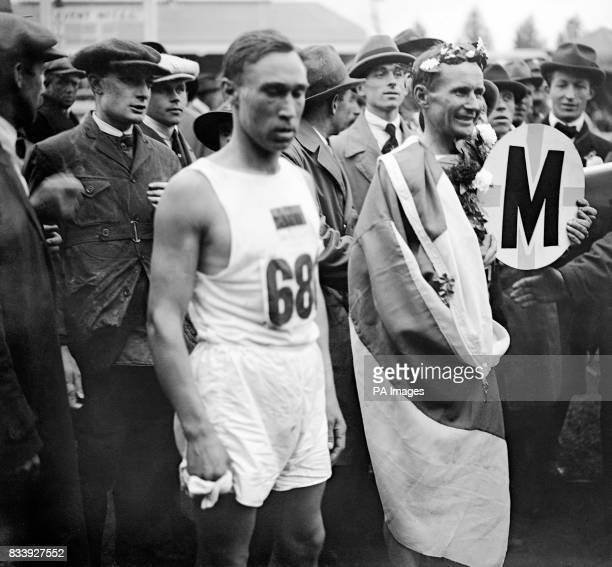 Hannes Kolehmainen of Finland draped in the Finnish flag and crowned with a wreath of laurels after winning the Marathon in 2 hours 32 minutes and 35...