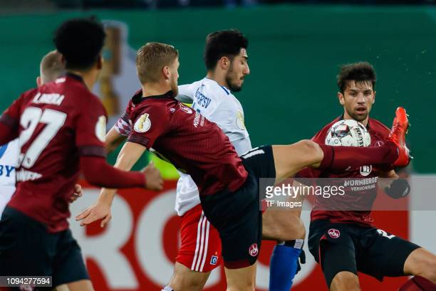 Hanno Behrens of 1 FC Nuernberg Berkay Oezcan of Hamburger SV and Lukas Muehl of 1 FC Nuernberg battle for the ball during the DFB Cup match between...