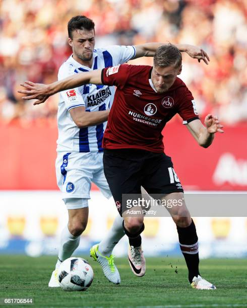 Hanno Behrens of 1FC Nuernberg is challenged by Jonas Meffert of Karlsruher SC during the Second Bundesliga match between 1 FC Nuernberg and...