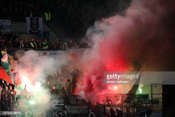 Hannover fans light flares during the Bundesliga match between 1 FSV Mainz 05 and Hannover 96 at Opel Arena on December 9 2018 in Mainz Germany