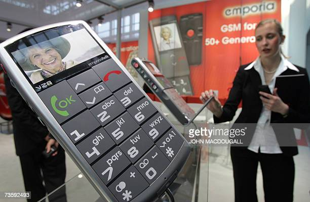 Sales representative shows visitors the Emporia mobile phones specially designed for people over 50 years of age at the CeBIT computer, digital IT...
