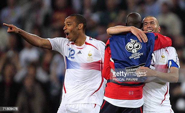French forward Thierry Henry and teammate midfielder Zinedine Zidane celebrate with teammate at the end of the World Cup 2006 round of 16 football...