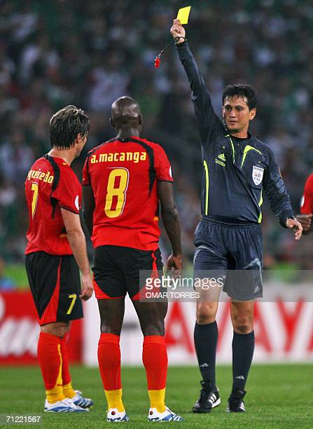 Singaporean referee Shamsul Maidin issues a yellow card to Angolan midfielder Andre during the 2006 World Cup Group D football match Mexico vs Angola...
