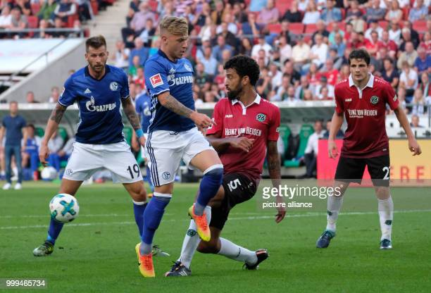 Hannover's Felipe and Schalke's Guido Burgstaller and Max Meyer vie for the ball during the German Bundesliga soccer match betweenHannover 96 and FC...