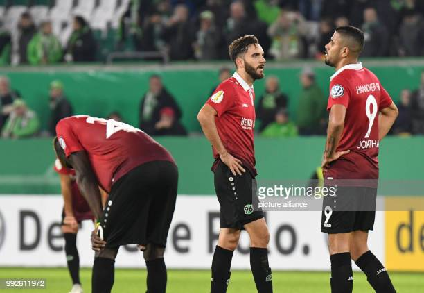Hannover's Salif Sane Kenan Karaman and Jonathas standing on the pitch after the DFBCup soccer match between VfL Wolfsburg and Hannover 96 in the...