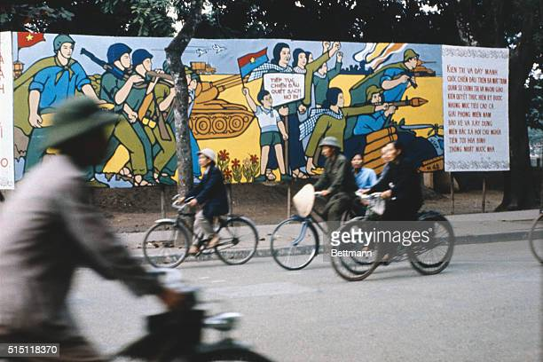 Civilians on bicycles ride past a colorful poster on a wall of Hanoi's main street protesting against South Vietnamese military activities and...