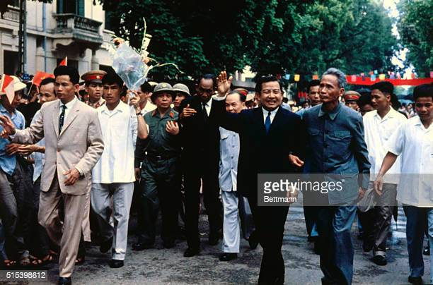 Hanoi, North Vietnam: Prince Norodom Sihanouk waves his hand during his arrival in Hanoi. At his right is North Vietnamese premier Pham Van Dong....