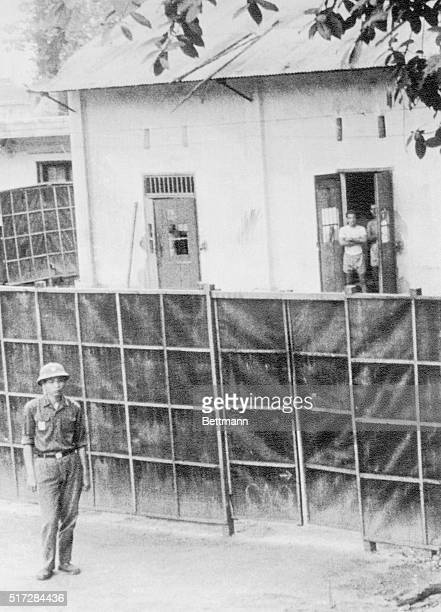 Hanoi North Vietnamese soldier stands guard outside Ly Nam de Prison better known as the Hanoi Hilton as yet to be released American POWs look out...
