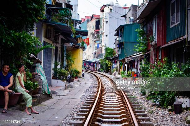 hanoi train street with railroad and residents sitting - hanoi stock pictures, royalty-free photos & images