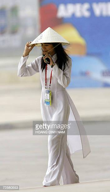 A volunteer in a traditional dress 'ao dai' and holding a conical hat walks inside the venue of the AsiaPacific Economic Cooperation summit 16...
