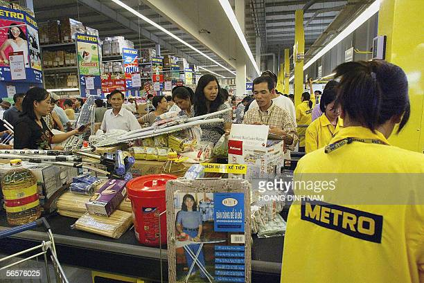FILES A picture taken on 31 July 2003 shows customers waiting at the checkout counter at the then newly opened Metro Cash and Carry wholesale center...