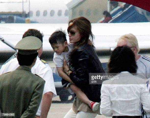 Hollywood movie star Angelina Jolie carries her newly adopted Vietnamese threeyearold son Pax Thien Jolie as she boards a jet at Hanoi's Noibai...