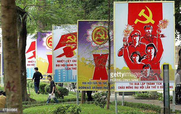 """Vietnam-politics-congress-corruption,sched-ADVANCER"""" People walk past a row of billboards installed at a public park to mark the up-coming national..."""
