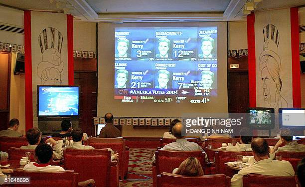 Hanoibased American and nonAmerican people sit watching the first resudlts in the US presidential elections on large screens in a room at Hanoi's...