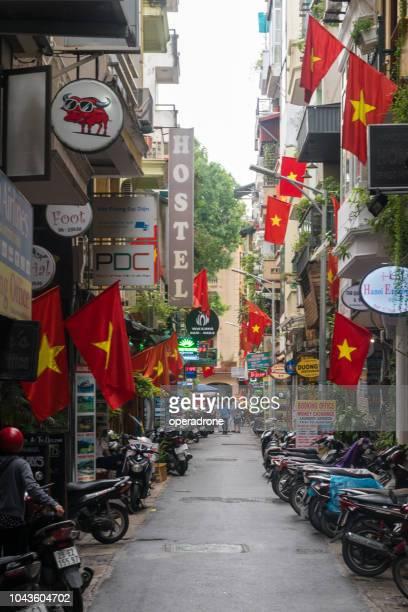 hanoi's old quarter street with vietnam's flags - ハノイ ストックフォトと画像