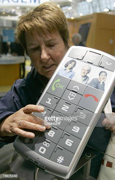 Woman inspects the mockup of a mobile phone with big-sized pressure keys equipped with braille made by Emporia 18 March 2007 at the CeBIT computer,...